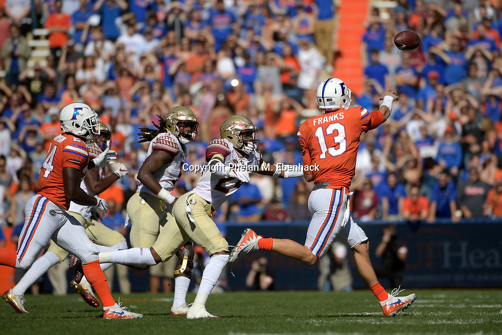 Florida quarterback Feleipe Franks (13) throws a pass while being pursued by Florida State defensive back Cyrus Fagan (24) during the first half of an NCAA college football game Saturday, Nov. 25, 2017, in Gainesville, Fla. (Photo by Phelan M. Ebenhack)