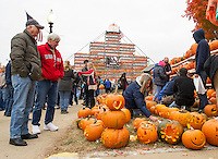 Jerry Vermette and Richard Lover watch as Claire Vermette lights candles for the pumpkins during Saturday's Pumpkin Fest in downtown Laconia.  (Karen Bobotas/for the Laconia Daily Sun)