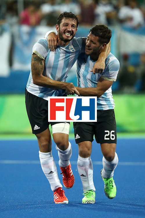 RIO DE JANEIRO, BRAZIL - AUGUST 18:  Manuel Brunet #24 of Argentina and Agustin Mazzilli #26 of Argentina celebrate winning the Men's Hockey Gold Medal match between Belgium and Argentina on Day 13 of the Rio 2016 Olympic Games at Olympic Hockey Centre on August 18, 2016 in Rio de Janeiro, Brazil.  (Photo by Sean M. Haffey/Getty Images)
