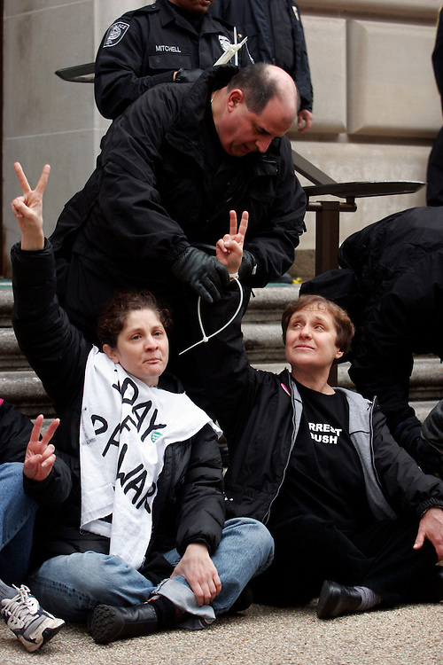 "Washington, Mar. 19, 2008 -Protesters are arrested in front of an entrance to the IRS headquarters in Washington on Wednesday, Mar. 19, 2008 in Washington.  The group is marking the 5th anniversary of the U.S. led invasion of Iraq with ""acts of civil disobedience."""