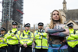 London, UK. 23rd April 2019. A climate change activist with messages painted on her arms stands in front of a police cordon in Parliament Square positioned to prevent fellow activists from Extinction Rebellion from attempting to deliver letters to Members of Parliament requesting meetings to discuss the issue of climate change.