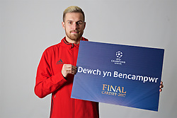 "CARDIFF, WALES - Friday, November 11, 2016: Wales' Aaron Ramsey holds up a board ""Dewch yn Bencampwr"" to encourage people to become volunteers for the 2017 UEFA Champions League Final in Cardiff. (Pic by David Rawcliffe/Propaganda)"