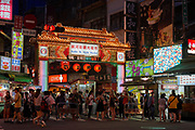 Tourists and locals walk around Raohe night market in the early evening. The market is one of the most popular in Taipei, with a wide variety of street food, stalls and games available.Each end of the market, which occupies a city street, features a traditional Chinese gate with the name of the market on it.