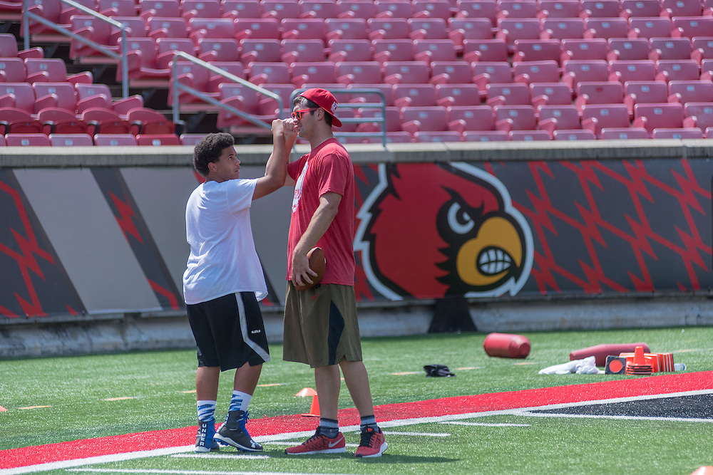 Donovan Pleasant, 13, an eighth-grader at Ramsey Middle School, fist bumps Gary Barnidge, a co-founder of the American Football Without Barriers youth football camp, after a one-on-one session at the University of Louisville's Papa John's Cardinal Stadium. June 25, 2016 June 25, 2016