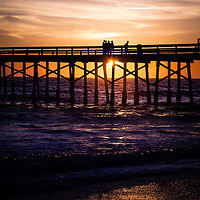 Photo of sunset over a pier in Orange County California. Photo is vertical, high resolution and has copy space for adding text.