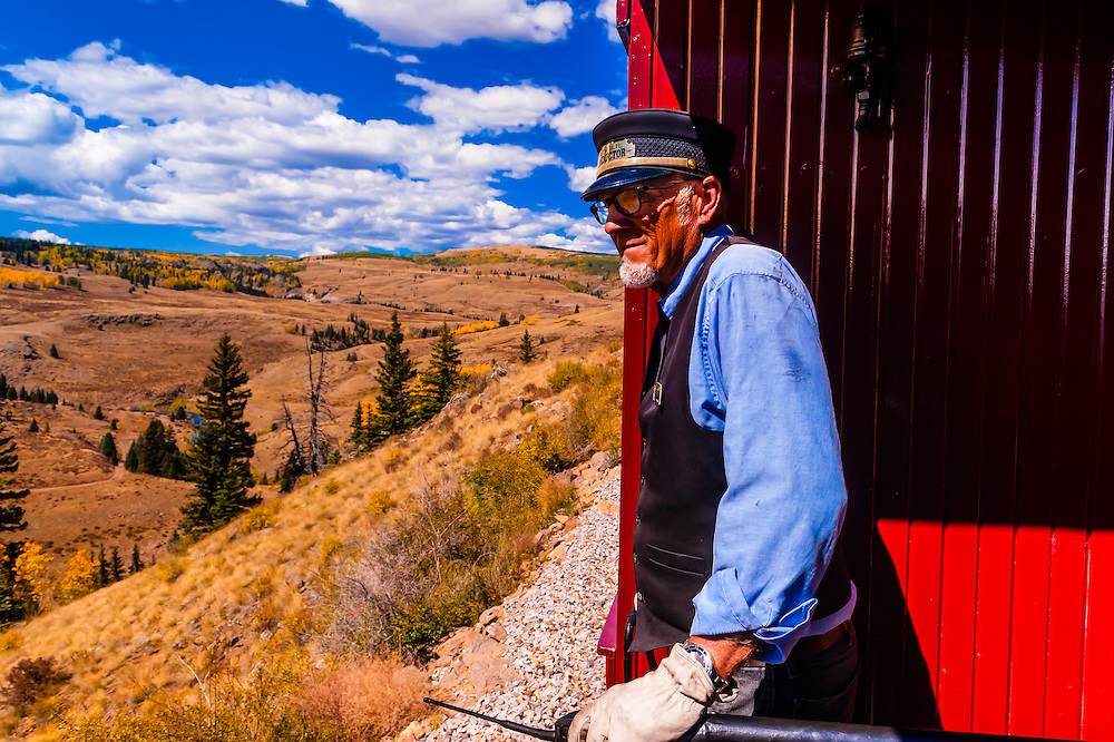 Train conductor on the Cumbres & Toltec Scenic Railroad train on the 64 mile run between Chama, New Mexico and Antonito, Colorado. The railroad is the highest and longest narrow gauge steam railroad in the United States. The train traverses the border between Colorado and New Mexico, crossing back and forth between the two states 11 times. The narrow gauge track is 3 feet wide. It runs over 10,015 ft (3,053 m) Cumbres Pass.