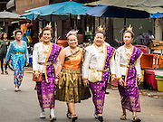 "23 JUNE 2015 - MAHACHAI, SAMUT SAKHON, THAILAND:  Thai women in traditional Thai dress walk through the Mahachai during the City Pillar Shrine procession. The Chaopho Lak Mueang Procession (City Pillar Shrine Procession) is a religious festival that takes place in June in front of city hall in Mahachai. The ""Chaopho Lak Mueang"" is  placed on a fishing boat and taken across the Tha Chin River from Talat Maha Chai to Tha Chalom in the area of Wat Suwannaram and then paraded through the community before returning to the temple in Mahachai.  PHOTO BY JACK KURTZ"