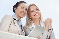 Low angle view of happy businesswomen with digital tablet looking away against clear sky