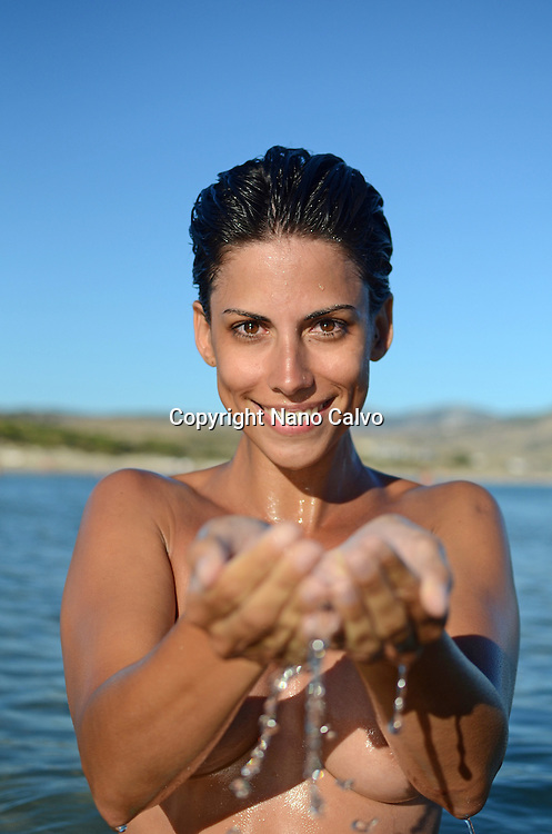 Young woman holds ocean water in her hands