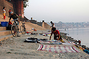 India, Uttar Pradesh, Varanasi man drying clothes on the Ganges River