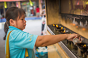 27 NOVEMBER 2012 - BANGKOK THAILAND:  A woman makes merit by pouring lamp oil into lamps at Wat Sri Boonreung on Klong Saen Saeb in Bangkok, Thailand.       PHOTO BY JACK KURTZ