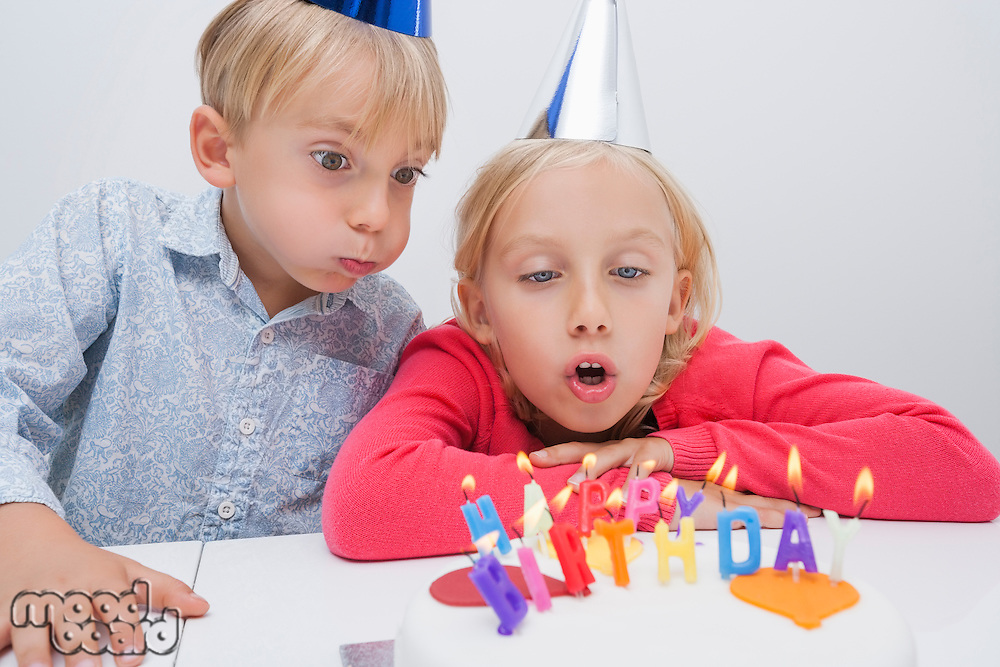Siblings blowing birthday candles at table