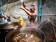 03 FEBRUARY 2019 - BANGKOK, THAILAND:A man pulls stewed ducks out of a vat in Bangkok's Chinatown district. The ducks were being stewed for Chinese New Year's banquets. Chinese New Year celebrations in Bangkok start on February 4, 2019. The coming year will be the Year of the Pig in the Chinese zodiac. About 14% of Thais are of Chinese ancestry and Lunar New Year, also called Chinese New Year or Tet is widely celebrated in Chinese communities in Thailand.          PHOTO BY JACK KURTZ