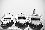 Varanasi, Three boats on the Ganges River, a young boy tries to catch a falling kite. Rendered in a sepia and purple split-tone.
