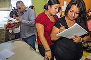 "18 AUGUST 2012 - PHOENIX, AZ:  People sign into the deferred action workshop at Neighborhood Ministries in Phoenix. More than 1000 people attended a series of 90 minute workshops in Phoenix Saturday on the ""deferred action"" announced by President Obama in June. Under the plan, young people brought to the US without papers, would under certain circumstances, not be subject to deportation. The plan mirrors some aspects the DREAM Act (acronym for Development, Relief, and Education for Alien Minors), that immigration advocates have sought for years. The workshops were sponsored by No DREAM Deferred Coalition. PHOTO BY JACK KURTZ"