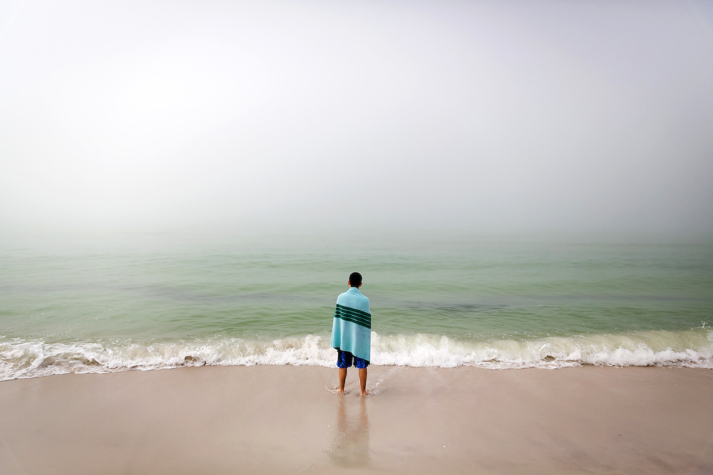 DAVID ALBERS/STAFF<br /> - Sam Balian, 19, of Westford, Mass., stands in the Gulf of Mexico as a fog rolls over the beach on Monday, Jan. 6, 2014, in Naples. Crews are mobilizing equipment at the beach access for an upcoming sand haul to the Pelican Bay beaches to the south.