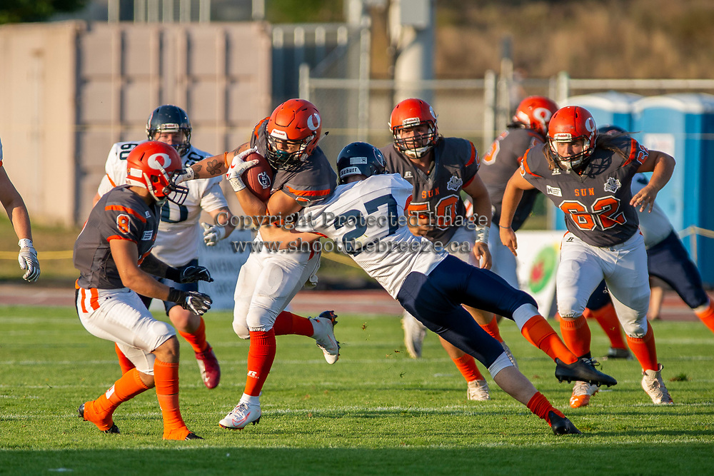 KELOWNA, BC - AUGUST 3:  Kelton Kouri #38 of Okanagan Sun is grabbed by Brody Rogers DB #27 Kamloops Broncos at the Apple Bowl on August 3, 2019 in Kelowna, Canada. (Photo by Marissa Baecker/Shoot the Breeze)