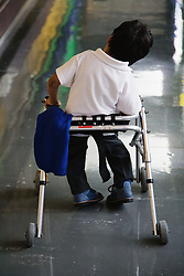 Boy with cerebral palsy using a walking aid,