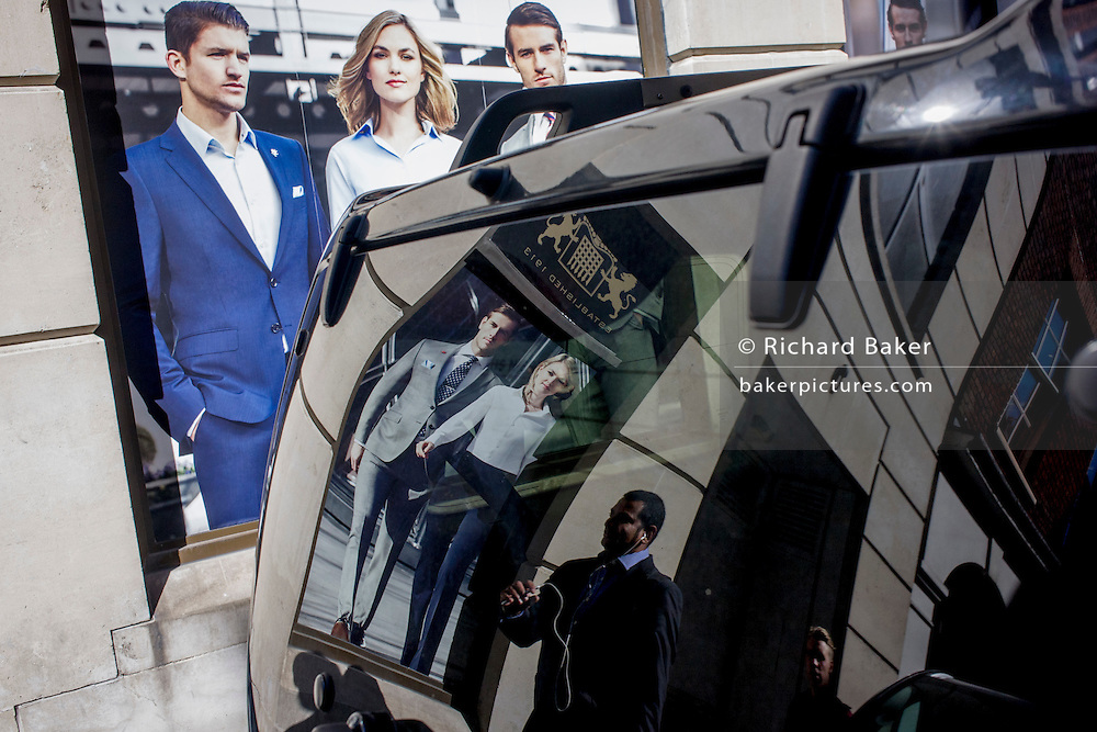 Models on a poster of a stylish clothing shop for business people are reflected in the rear of a black vehicle parked in the City of London.