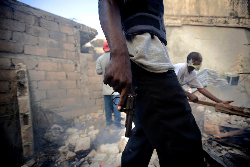 A private security guard runs amid a burning store as he disperses residents in downtown Port-au-Prince, Haiti on January 18, 2010.