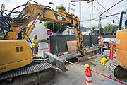 Workers use an excavator to help remove material around utilities in a trench just south of Brannan on 4th.
