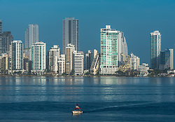 A small boat sails on the blue waters of Cartagena Bay with the city's skyscrapers gleaming in the background.