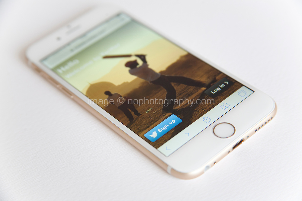 Gold and white Apple iPhone 6 with a Twitter log in page against a white background