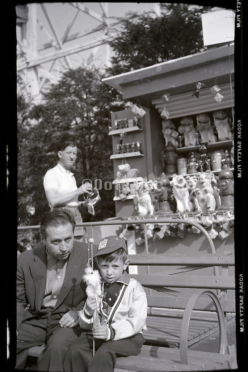 father posing with son on a day outing at a fair ground USA 1950s