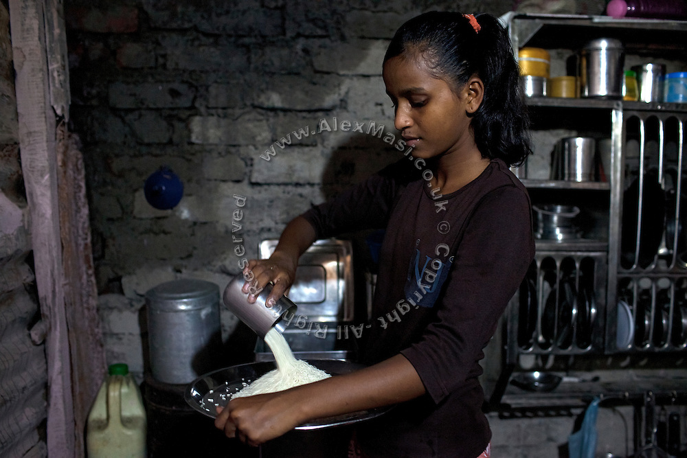 Mayuri Mahesh Pandit, 13, (centre) is pouring some rice to be cooked for lunch before leaving to participate at the Unicef-run 'Deepshikha Prerika' project inside the Milind Nagar Pipeline Area, an urban slum on the outskirts of Mumbai, Maharashtra, India, where she resides with her family.
