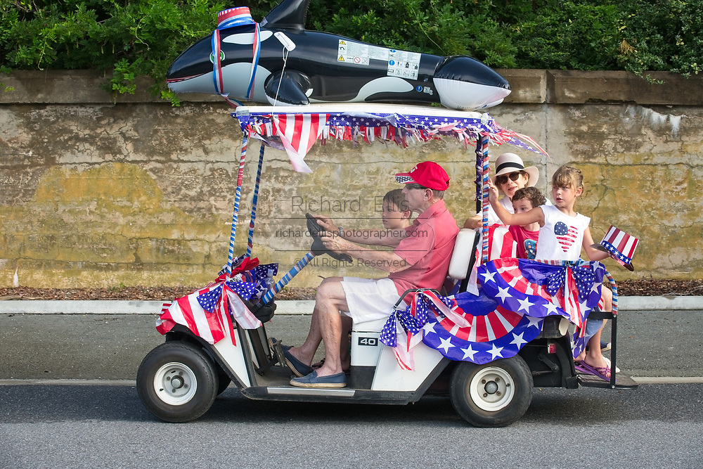 A family rides along in a golf cart decorated in patriotic bunting and a killer whale during the annual Sullivan's Island Independence Day parade July 4, 2017 in Sullivan's Island, South Carolina. The tiny affluent sea island hosts a bicycle and golf cart parade through the historic village.