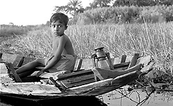 BANGLADESH BARISAL DISTRICT KURULIA SEP94 - A Bengali boy sits on an old boat carrying a petrol lamp at dusk. Boats are the only means of transport in the swamps of the Ganges River Delta...The Bangladesh Bureau of Statistics estimates the total working child population between 5 and 17 years old to be at 7.9 million...jre/Photo by Jiri Rezac..© Jiri Rezac 1994