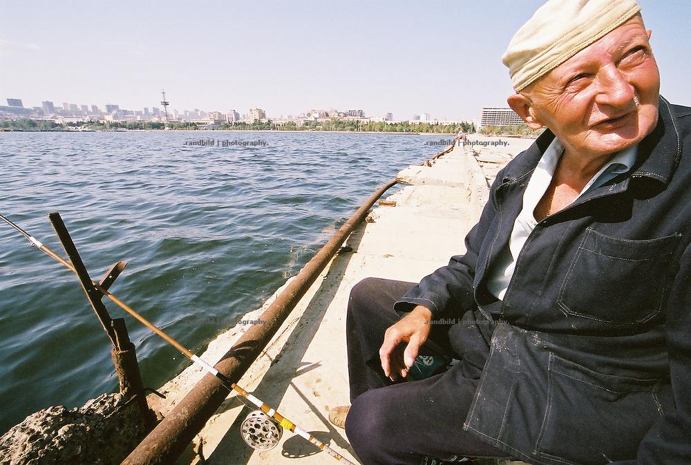 Im Hafen der aserbaidschanischen Hauptstadt Baku angeln auf einer Kaimauer alte Herren. Das Wasser ist von der Ölförderung im Kaspischen Meer verschmutz. Entsprechend keine Fische gehen ihnen an den Haken...Fisherman in the harbour of Baku, Aserbaijan.