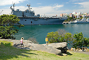 Two children looking across Woolloomoolo Bay to Garden Island Naval Base, The Domain, Sydney, Australia