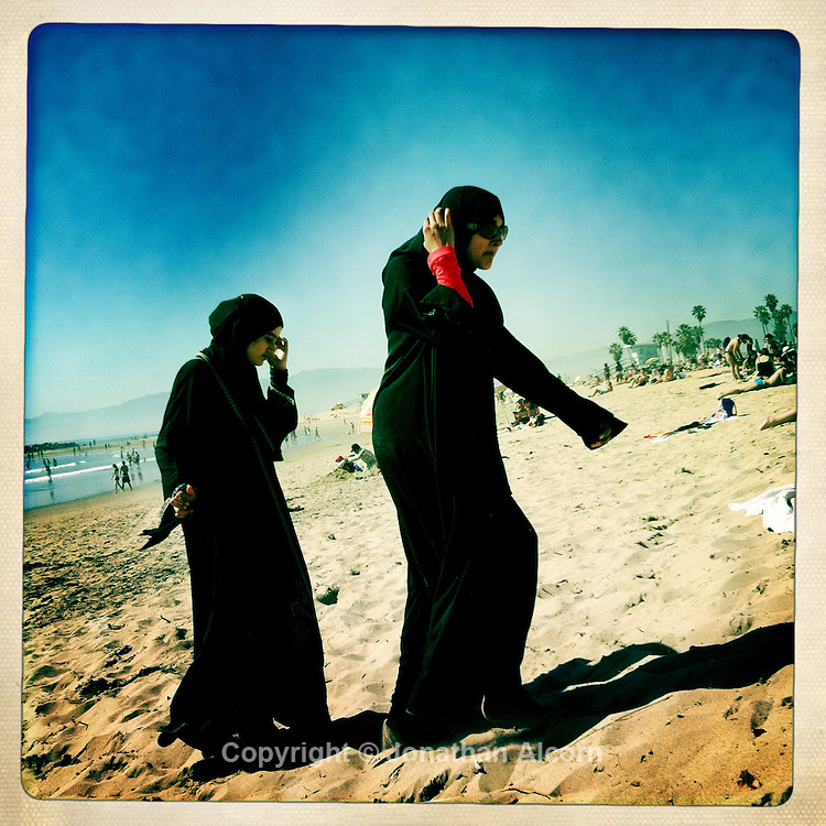 Two muslim women both wearing the traditional hijab and burqa walk on the sandat Venice Beach as a record of 92 degrees was set in downtown Los Angeles today, according to the National Weather Service breaking a 45 year old record. Two muslim women both wearing the traditional hijab and burqa walk on the sand