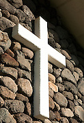 A white cross on a stone wall on Molokai.
