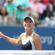 Caroline Wozniacki, Denmark, hits balls into the crowd after her victory against Jamie Loeb, USA, on Arthur Ashe Stadium in the first round of the Women's Singles during the US Open Tennis Tournament, Flushing, New York, USA. 1st September 2015. Photo Tim Clayton