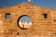 A round window in a stone wall at the Skala du Port, provides a glimpse of the city of Essaouira, Morocco
