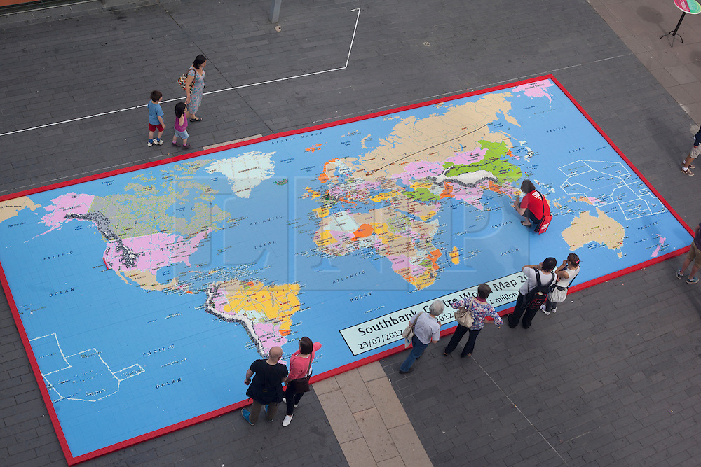 © licensed to London News Pictures. London, UK 13/08/2012. People admiring a giant map of the world, measuring 12 by 5 metres, made from over a million Lego bricks by members of public and designed by Duncan Titmarsh for the Festival of the World at Southbank Centre. Photo credit: Tolga Akmen/LNP
