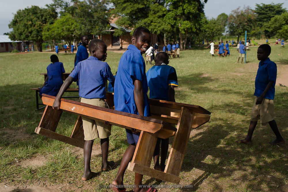 Students moving desks at Agwait Primary School near Tororo in Eastern Uganda on 1 August 2014.