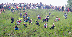 © Licensed to London News Pictures 26/05/2018, brockworth, Gloucester, UK. The annual cheese rolling race held at Coopers Hill, Brockworth outside Gloucester. Competitors race down the extremly steep slippery hill chasing a double Gloucester cheese, the winner of each race recieves the cheese as thier prize. Pictured here :  fenale competitors on the hill during the ladies race - Photo Credit : Stephen Shepherd/LNP