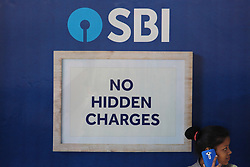 March 27, 2019 - Mumbai, India - A girl talks on a mobile phone in front of a logo of State Bank of India (SBI) in Mumbai, India on 27 March 2019. As the India's largest bank State Bank of India has a network of more than 43,000 automated teller machine (ATM) in India, which is largest network of ATMs offered by any other bank in the country. (Credit Image: © Himanshu Bhatt/NurPhoto via ZUMA Press)