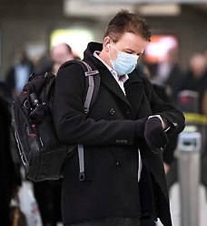 © Licensed to London News Pictures. 10/03/2020. London, UK. A commuter checks his watch while wearing a medical mask at Westminster Underground Station in central London. New cases of the COVID-19 strain of Coronavirus are being reported daily as the government outlines it's plans for controlling the outbreak. Photo credit: Ben Cawthra/LNP