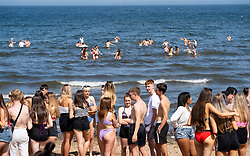 Edinburgh, Scotland, UK. 31 July, 2020. Temperature of 25C and sunshine brought huge crowds to Portobello Beach outside Edinburgh. Several large groups of teenagers were enjoying beach and alcoholic drinks were very popular. Iain Masterton/Alamy Live News