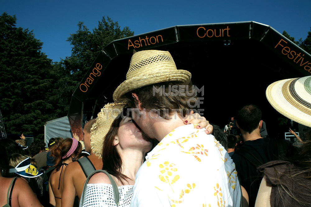 A couple in straw hats, kissing at Ashton Court Festival, 2006