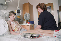 Young boy with Crohn's disease lying in hospital bed on Children's ward talking to his mother,