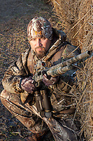 DEER HUNTER WITH A MOSSBERG SHOTGUN WEARING REALTREE CAMOUFLAGE SHOOTING FROM BEHIND HAY BALES