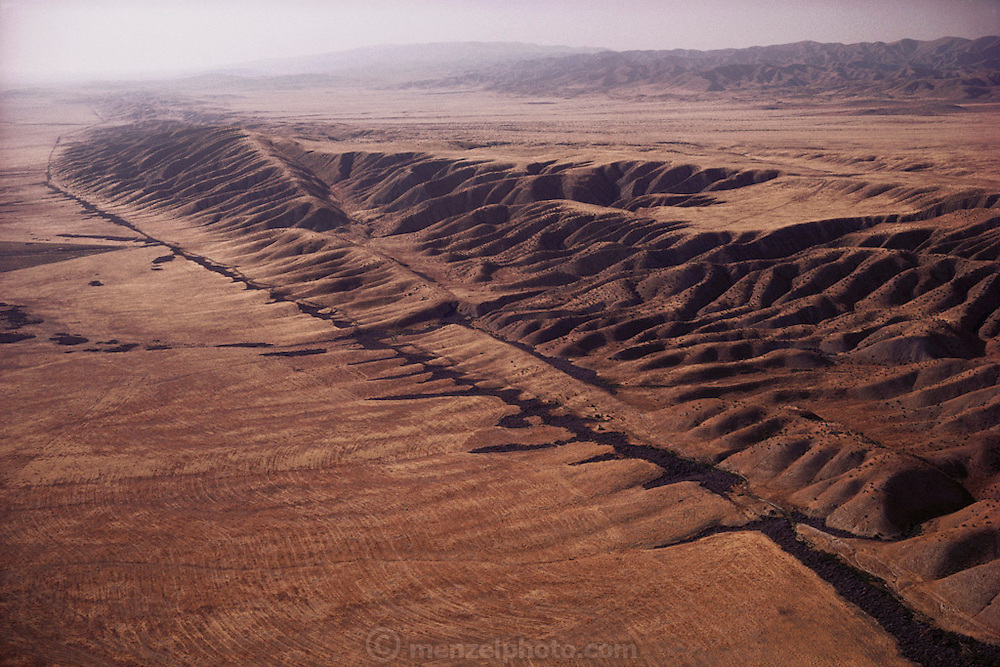 "Aerial photograph of the San Andreas Fault in California as it crosses the Carrizo Plain. The Earth's crust is fractured into a series of ""plates"" that have been moving very slowly over the Earth's surface for millions of years. Two of these moving plates meet in western California; the boundary between them is the San Andreas fault. The Pacific Plate (on the west) moves northwestward relative to the North American Plate (on the east), causing earthquakes along the fault. The San Andreas is the ""master"" fault of an intricate fault network that cuts through rocks of the California coastal region."