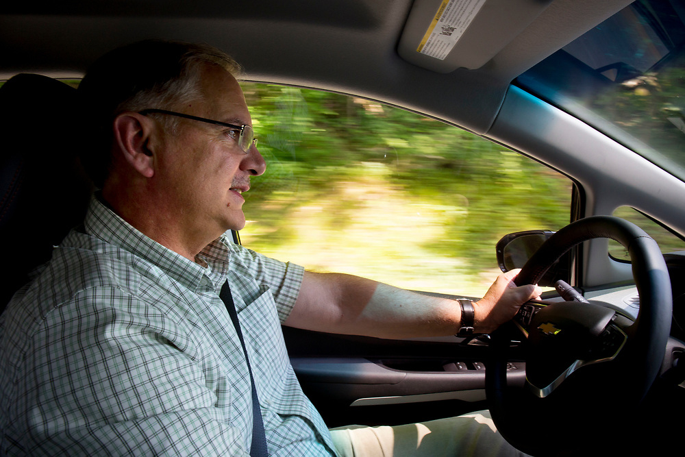 Kevin Jones, of Chittenden, Vt., commutes to work in his electric car, a Chevy Bolt, in Royalton, Vt., on July 12, 2017. Jones is director for the Institute for Energy and the Environment at Vermont Law School. (Photo by Geoff Hansen)