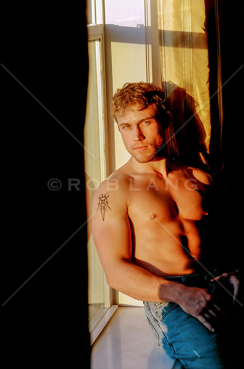 All American sexy man without a shirt sitting by a window at sunset