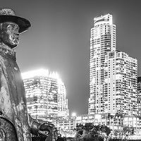 Stevie Ray Vaughan Memorial bronze statue and the Austin, Texas skyine at night black and white panorama photo.